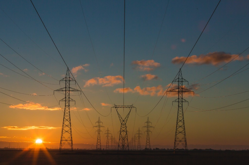 Electricity towers with sunset and sky behind